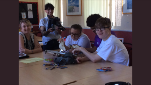 Three young people are sat at a table exploring objects while a scriptwriter looks on and a camera person films