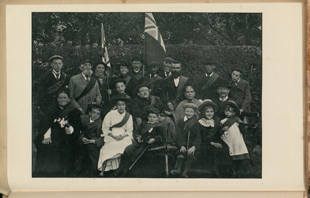 older guild members in front of a hedge in a garden