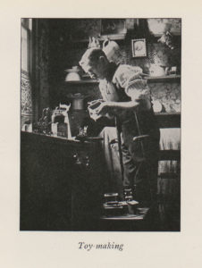 Image shows man in Edwardian style room leaning over a counter to make toys