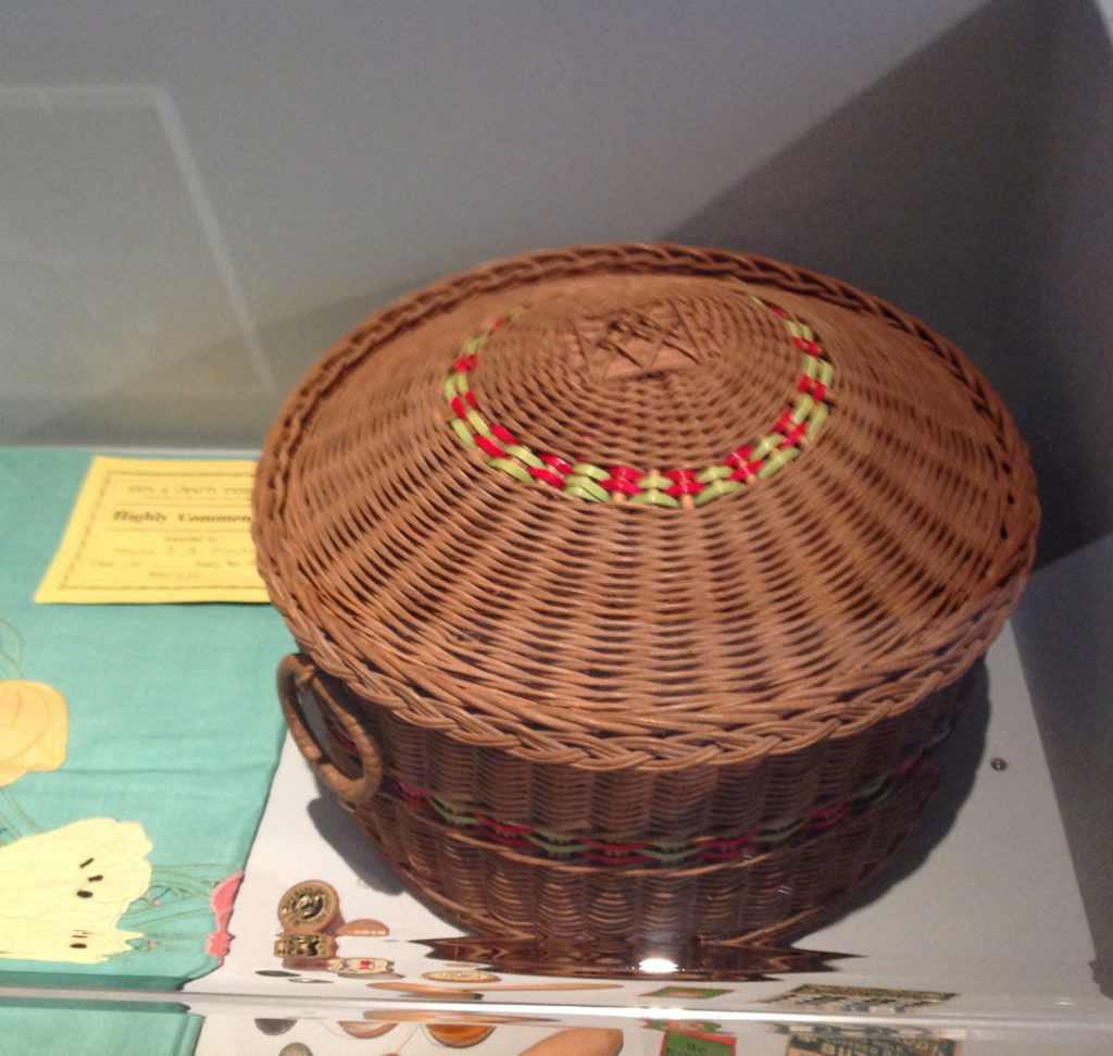 Image shows round brown basket with red and yellow decoration in the lid.