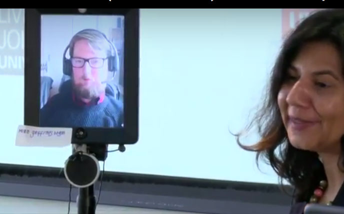 Man in headphones seen through TV screen attached to robot with woman onstage at symposium