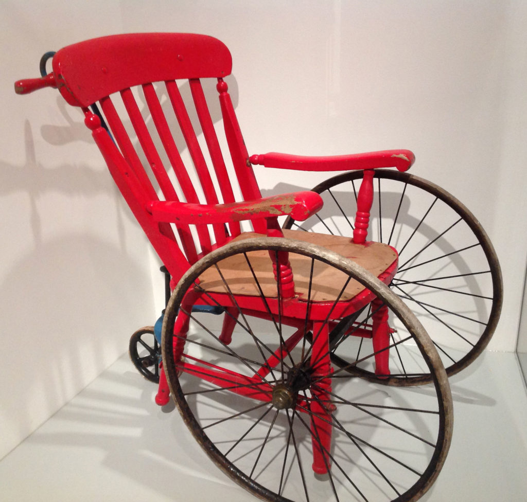 Red painted wooden chair mounted on wheels