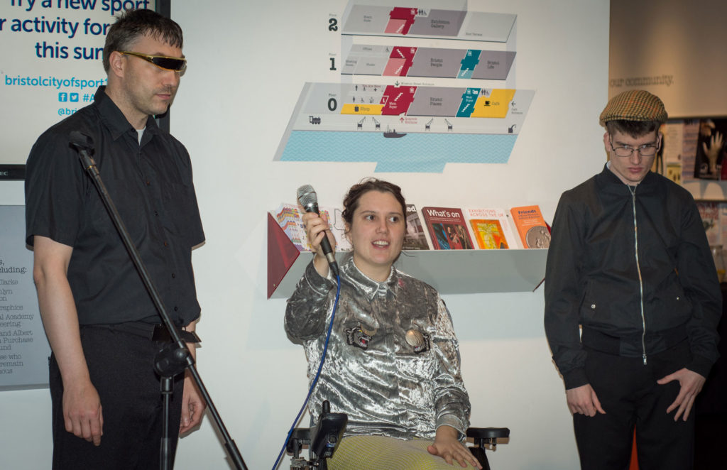 woman with microphone and two men at the launch of the M Shed exhibition