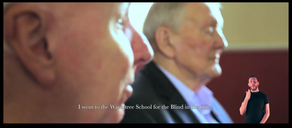 Man doing BSL superimposed on two older men giving an oral history interview