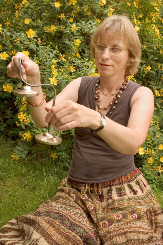woman sits in garden holding two small chimes on a cord.