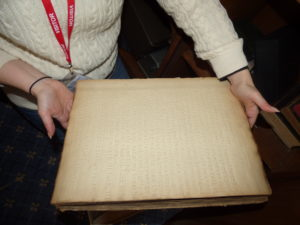 The image shows two hands holding the oversized and thick book which is about the size of a modern laptop