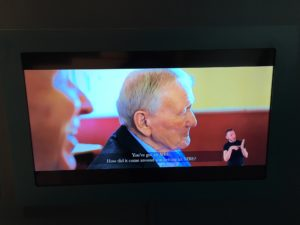 The image shows a tv screen which is showing the film Visions which was created by blind and visually impaired students at St Vincents School for Sensory Impairment. On the screen are two older men who are both laughing plus the subtitles of what is being said and BSL interpretation.