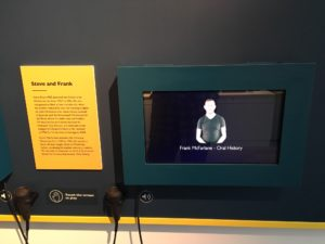 The image shows a tv screen with a handheld speaker next to it. On the screen is a BSL speaker who interprets the audio.