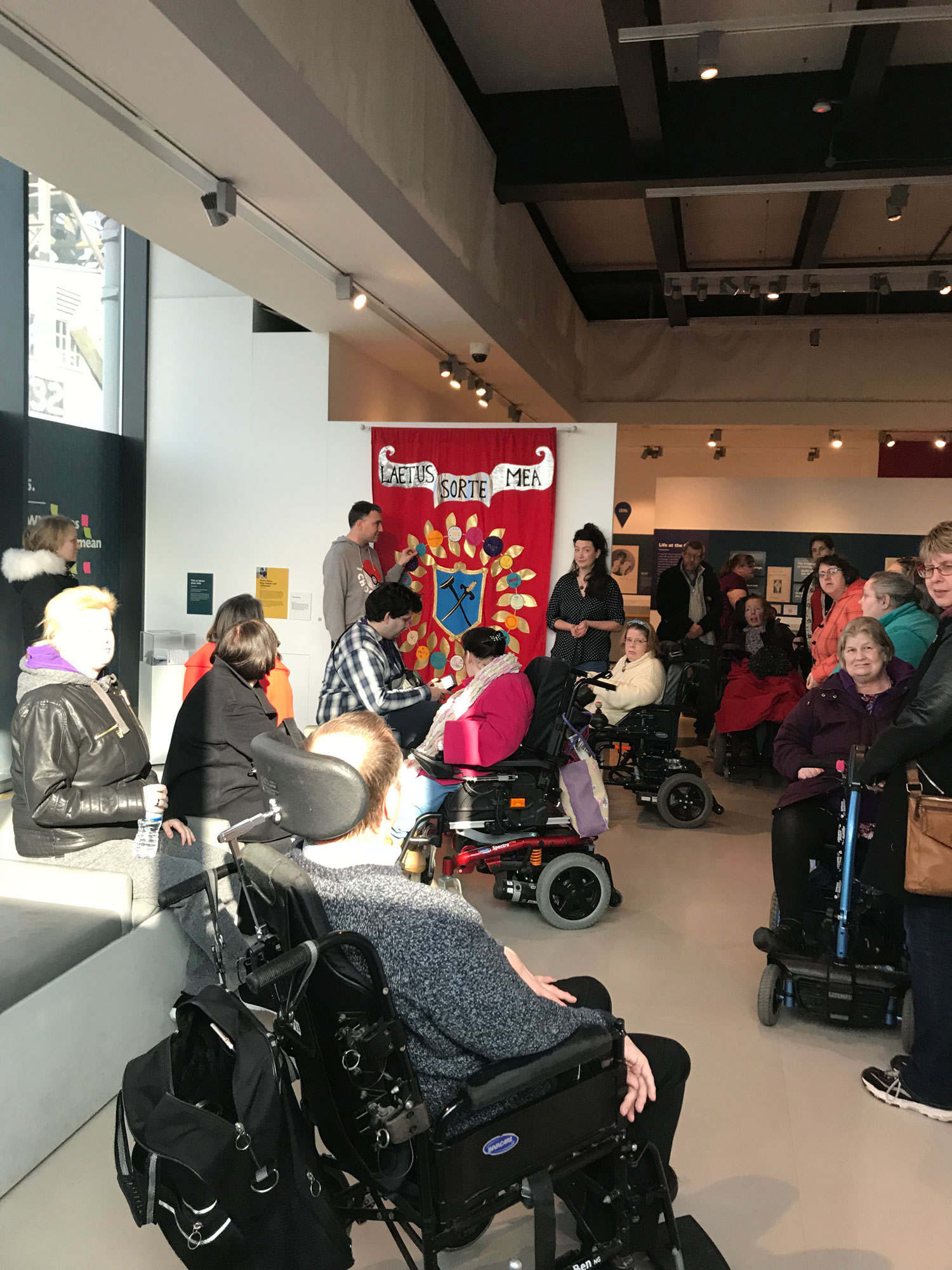 Group of people from Wecil sit in front of the banner made for the Mshed exhibition.