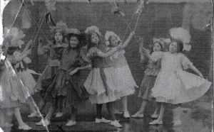 Girls holding ribbons on sticks and dressed in frocks which may be made of paper for dressing up