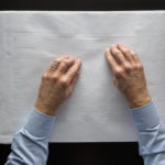 Man's hands on white sheet of paper with raised dots and shapes to indicate building outline and features