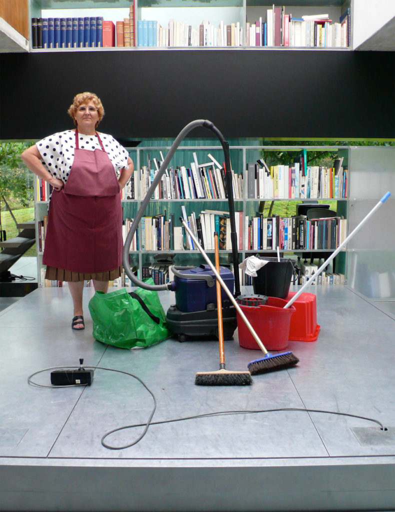 Woman with cleaning equipment stands on the large moving platform between floors